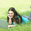 portrait of a cute young female lying on the grass in the park using a lapt — Stock Photo