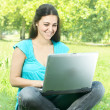 Portrait of a cute girl sitting on the grass in the park using a laptop — Stock Photo #6039809