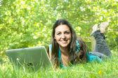使用を lapt 公園の芝生の上に横たわってかわいい若い女性の肖像画 — ストック写真