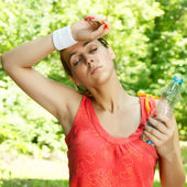 Fitness girl resting after exercising outdoors. — Stock Photo