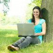 Happy young woman using laptop outdoors — Stock Photo