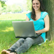 Royalty-Free Stock Photo: Happy young woman using laptop outdoors