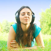 Relaxed girl with headphones listen the sounds of nature — Stock Photo