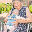 Grandmother holding her granddaughter - Stock Photo