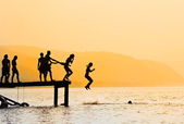 Silhouettes of kids who jump off dock on the lake — Stock Photo