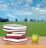 Books and green apple on desk — Stock Photo