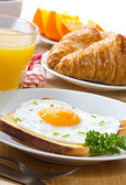 Breakfast with fried egg, juice and croissant — Stock Photo