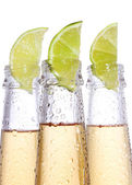 Bottles of beer with lime — Stock Photo