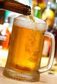 Beer pouring into mug — Stock Photo