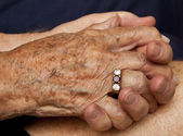 Old couple holding hands — Stock Photo