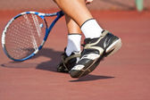 Tennis player legs and feet on court — Stock Photo