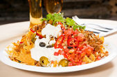 Fresh nachos and vegetable salad with meat — Stock Photo