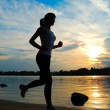 Stock Photo: Silhouette of beautiful woman running on sunset