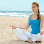 Beautiful woman practice yoga on the beach — Stock Photo