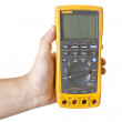 Hand holding electronic multimeter — Stock Photo #5392146