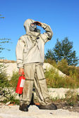 Man in protective suit and a fire extinguisher looks into the distance — Stock Photo