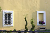 White window on yellow wall — Stock Photo