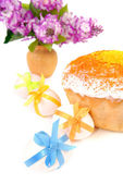 Easter cake and eggs decorated with bows. Vase with a lilac bouq — Stock Photo