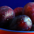 Royalty-Free Stock Photo: Plums. Fresh ripe washed plums in a ceramic bowl close-up on a b