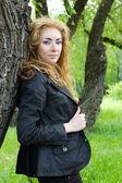 Redheaded woman near tree — Stock Photo