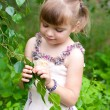 Cute girl in park is considering young leaves — Stockfoto #6111175