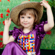 Cute girl in a purple dress and a straw hat — Stock Photo