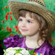 Cute girl in a purple dress and a straw hat with flowers — Stock Photo
