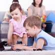 Boy  and baby girl playing computer — Stock Photo