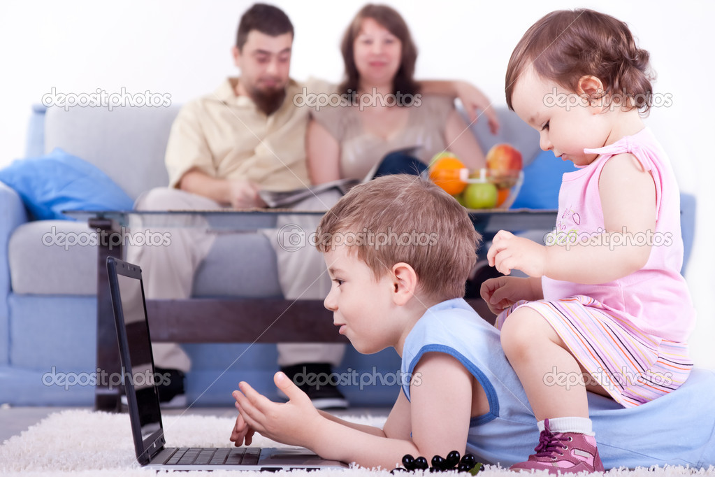 Baby girl and little boy playing on lap top in living room  Stock Photo #5514171