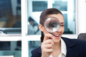Researching smiling business woman with loupe — Stock Photo