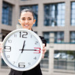 Beautiful attractive woman holding a clock — Stock Photo