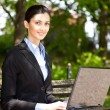 Overworked businesswoman in nature — Stock Photo