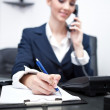 Businesswoman writing an appointment and using phone — Stock Photo