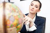 Businesswoman in office looking globe — Stock Photo