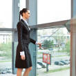 Businesswoman standing inside her office building - Stock Photo