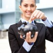 Business woman putting coins money in piggy bank - Stock Photo