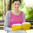 Smiling girl on bench in park reading — Stock Photo