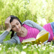 Stock Photo: Girl lying on grass in park with book and headset
