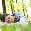 Stock Photo: Tired student girl lying on grass