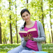 Stock Photo: Girl reading a book in park