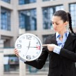 Business woman holding analog clock — Stock Photo