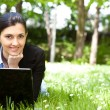 Young woman working on laptop in the field — Stock Photo #5722808