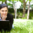 Young woman working on laptop in the field — Stock Photo