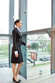 Businesswoman standing inside her office building — Stock Photo