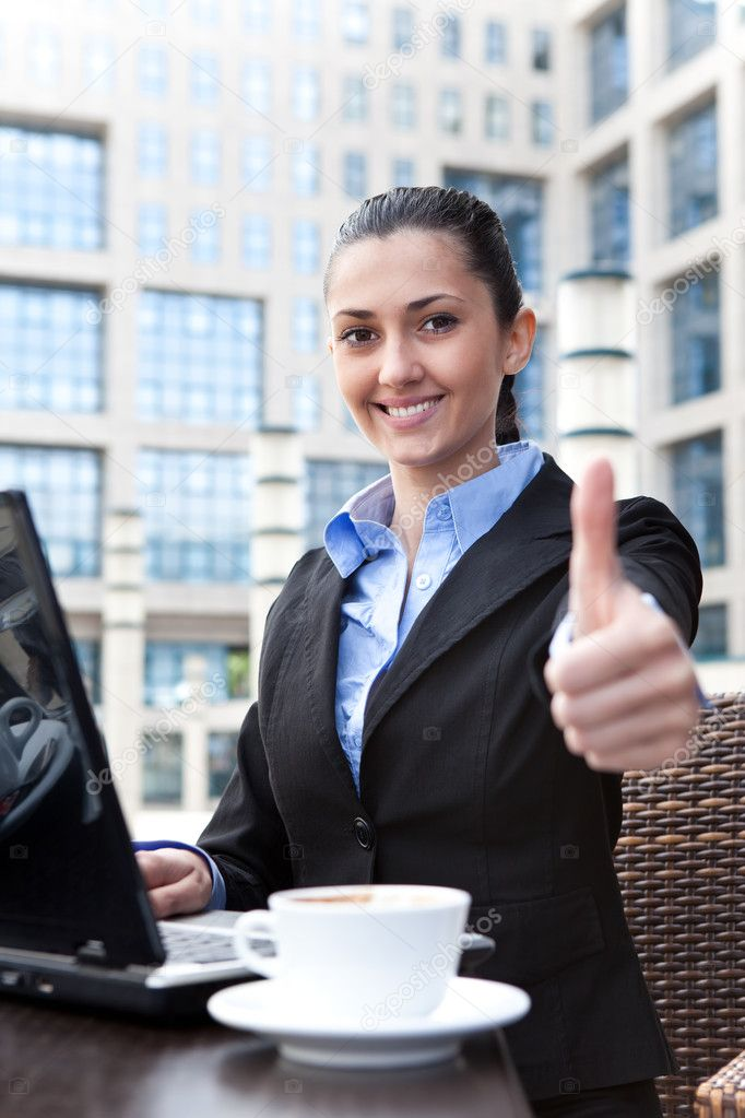 Smiling business woman working on laptop and shoving thumbs up — Stock Photo #5721598