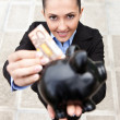 Businesswoman putting money in piggy bank — Stock Photo