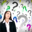 Businesswoman with question marks — Stockfoto