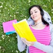 Stock Photo: Girl reading a book and listening music in park