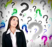 Businesswoman with question marks — Stock Photo