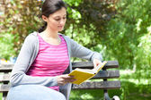 Girl in park reading book — Stock Photo
